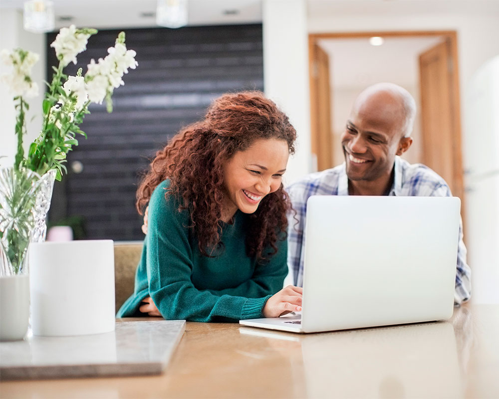 woman and man laughing in front of computer
